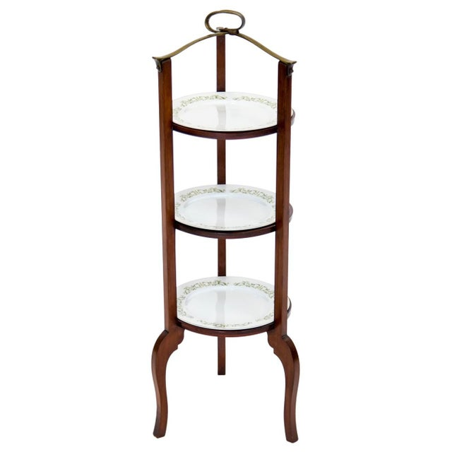 Mahogany butler's stand with a decorative brass handle and three circular open shelves holding porcelain plates. The solid...