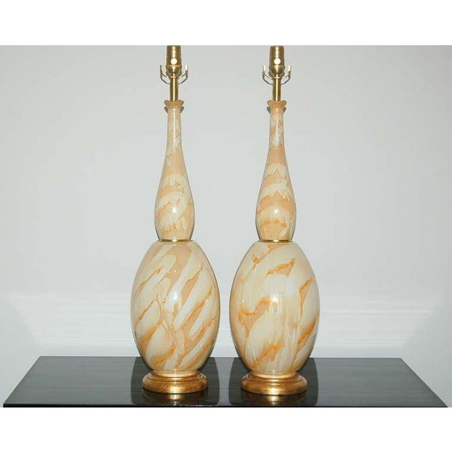 Tulip-topped pair of vintage hand blown Italian glass table lamps cinched at the waist with brass. The glass has swirls of...