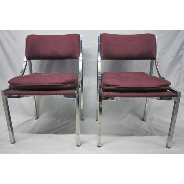 Pair of Dining chairs by Milo Baughman featuring mirror finished steel frame and vintage bordeaux silk upholstery. One of...