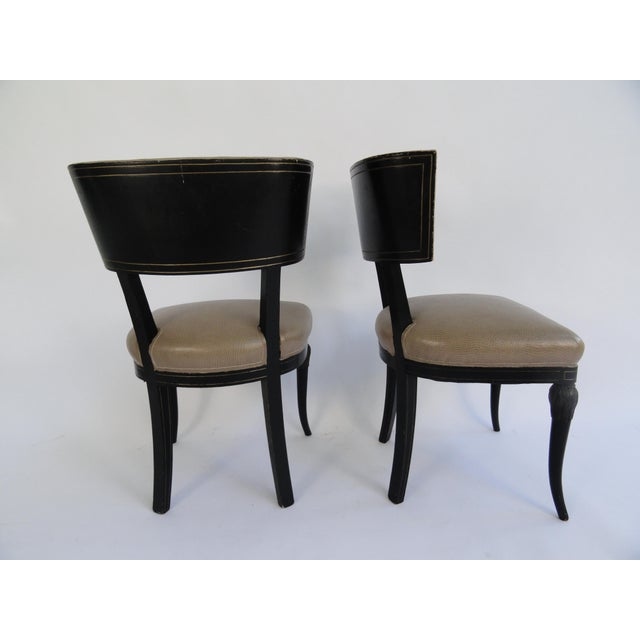 Set of four Maison Jansen side chairs with original ebony finish with gilt detail. Upholstered in faux ostrich.