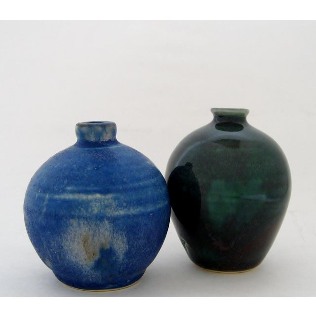 Two artisan ceramic mini vases; one in a blue satin glaze with ecru mottling, one in green gloss glaze with hints of...