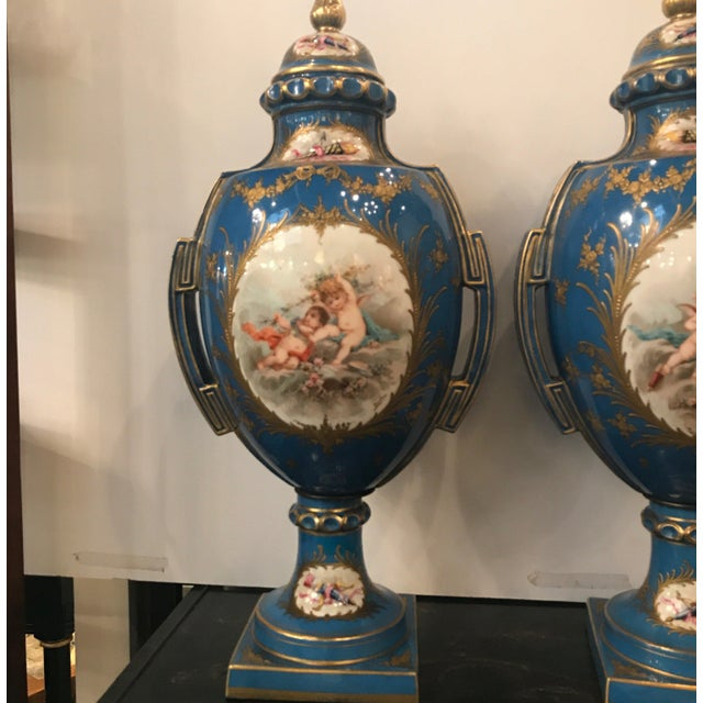 A pair of Celeste blue porcelain urns with romantic cartouch panels of putti on the fronts and backs. The panels with had...