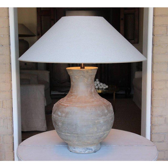 A large Chinese Han dynasty unglazed terracotta jar, 'Hu,' that has been mounted as a table lamp. Unglazed pottery like...