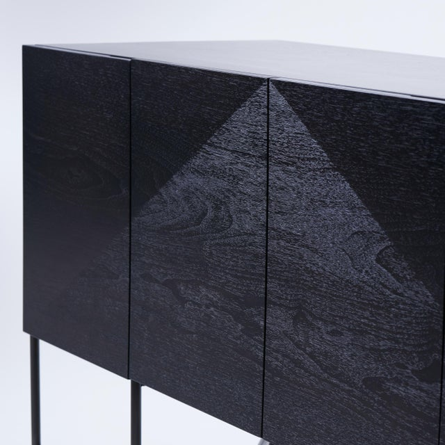 Shown in patinated welded steel and stained walnut. The central triangular detail has been wire-brushed to raise the...