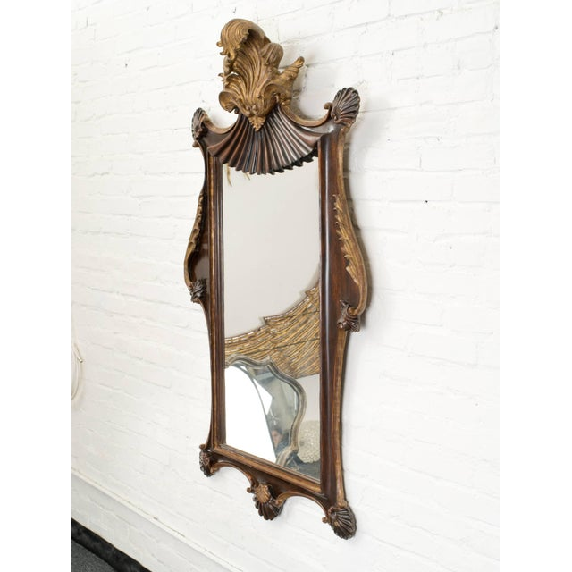 Giltwood and polished mahogany frame with hand-carved leaves and scrolls. circa 1920s.
