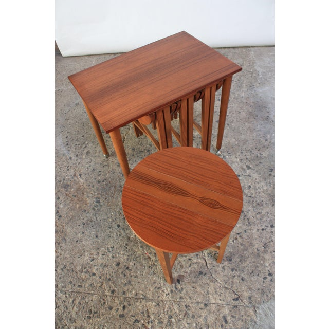This teak set, which includes a serving table on caster wheels and four drop-leaf nesting tables, is in the style of the...