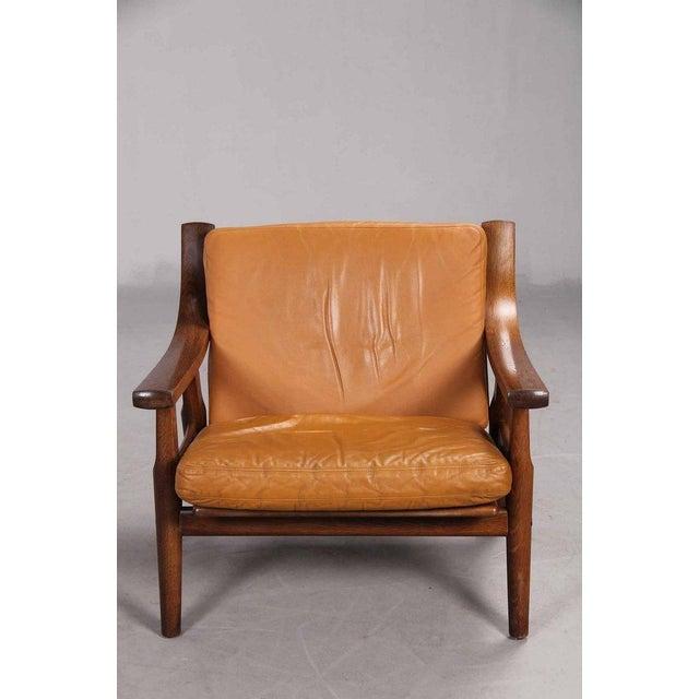 Low-backed armchair designed by Danish designer Hans Wegner in 1973. The frame of dark-stained oak with spoke back. The...