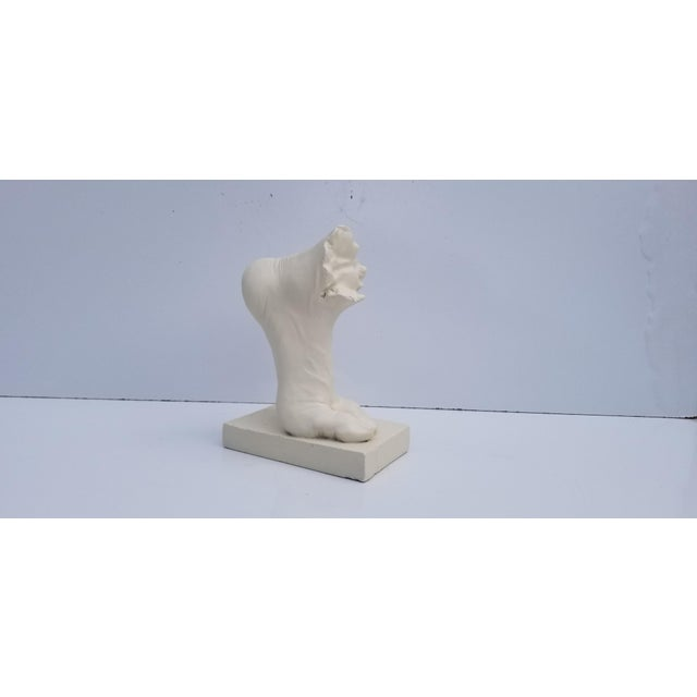 This is a piece of modern art from the mid 20th century. The sculpture is of a foot casted in plaster. Signed: TMS and...