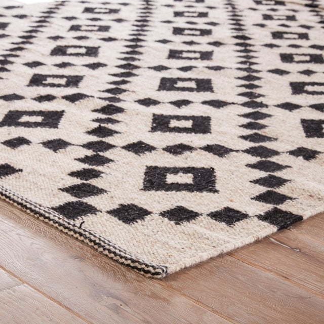 A modern twist on traditional flatweave style, this sleek layer showcases a black trellis design on a natural undyed wool...
