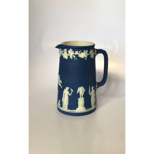 Beautiful antique Wedgwood Jasperware pitcher in dark blue with white raised classical figure accents. Excellent condition.