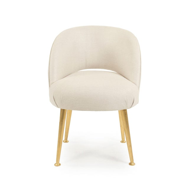 Plush curved back chair upholstered in an off-white linen on gold legs.