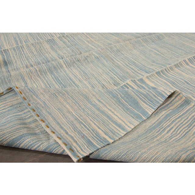 A hand-knotted Kilim rug with a stripe design on a beige field. Accents of blue and ivory throughout the piece This rug...