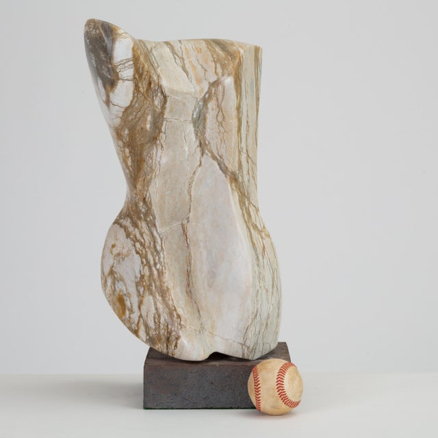 A spectacularly veined gray marble sculpture, touched with notes of ochre and cinnamon. The abstracted form, mounted on a...