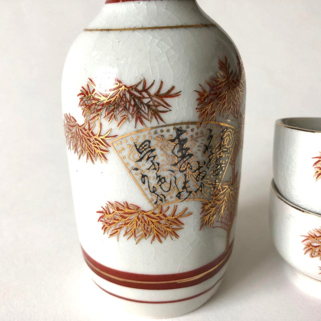 Vintage ceramic Japanese sake decanter set with 2 sake cups. The set features red and gold bamboo tree motifs and is...