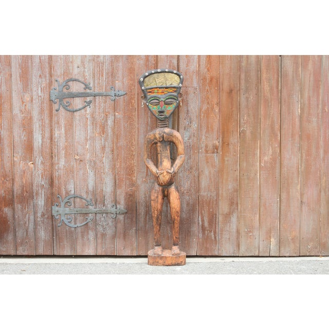 A life size wooden figurine from Bamum in Cameroon. Bamum craft artists created this with beads and metal embossed accent...