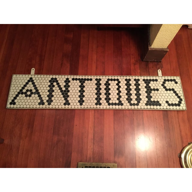 """White & black tile sign that says """"ANTIQUES"""" framed in white wood. Tiles are clean with a few non-distracting marks. Great..."""