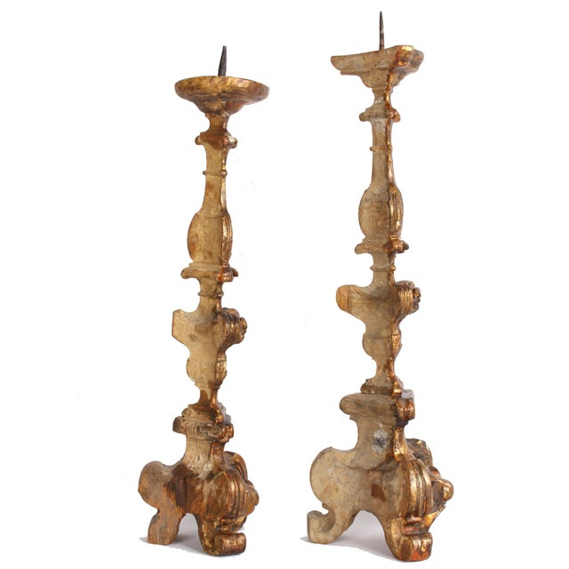 Two delicately carved and gilded wood Italian altar candlesticks that while are not an exact pair, certainly belong...