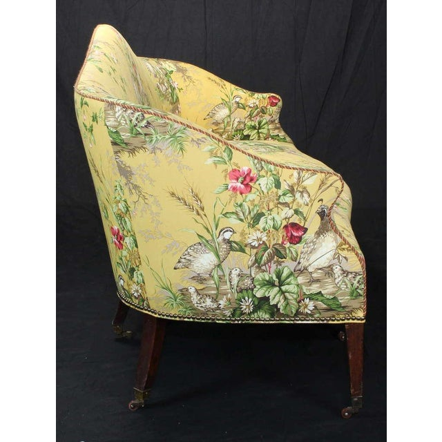 An elegant and comfortable early 19th century sofa with gently curving back and seat covered in a rich yellow cotton...