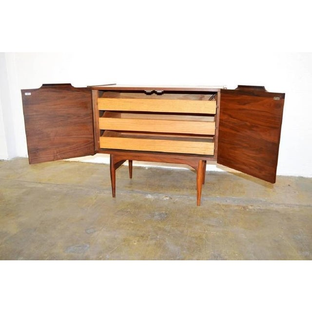 Stunning vintage walnut chest designed by John Keal for Brown Saltman. Features bi-folding doors concealing three drawers....