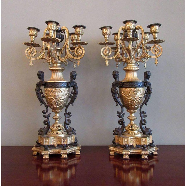 A pair of 19th century French neoclassical patinated and bronze doré candelabras, circa 1840, with five foliate cast...