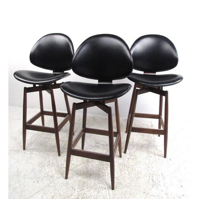 This unique set of three vintage barstools features a beautiful sculpted seat shape which wonderfully combines style and...