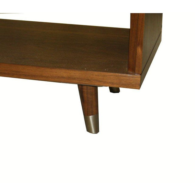 Walnut and parchment one-drawer nightstands on solid tapered walnut legs detailed with brass sabots. Custom embossed...