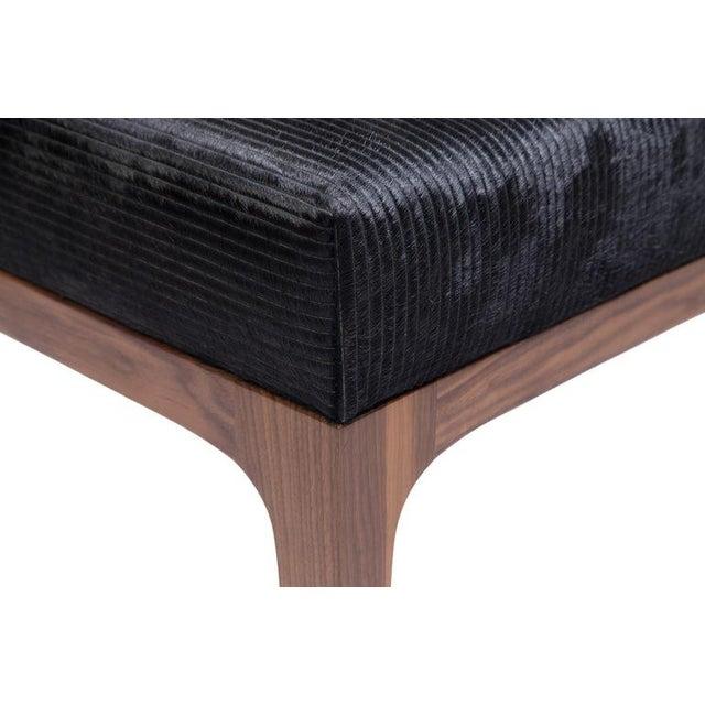 THE RAPHAEL OTTOMAN – mid-century modern style laser cut stripe pattern cowhide ottomans shown in black -Laser cut stripe...