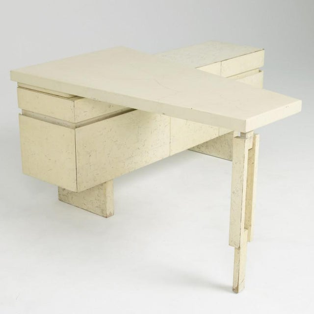 The pictured desk features a case in a faux-limestone finish and a desktop in an ivory crackle lacquer finish. The case...