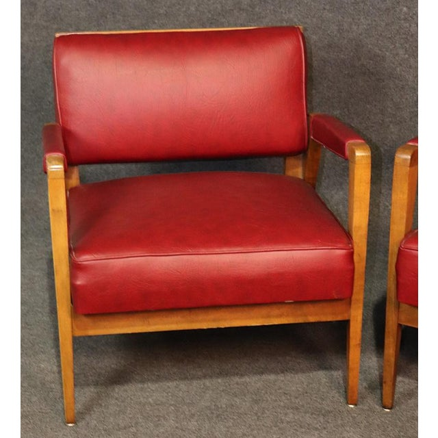 Pair of Mid-Century Modern curved solid tiger maple framed chairs with leather upholstery.