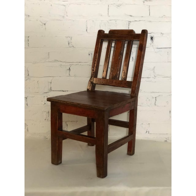 Early 20th Century Qing style child's chair with a slat back and solid seat. Made from teak.
