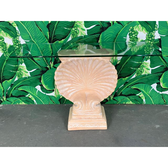 Hollywood Regency shell form console table in the manner of Edward Wormley features glass top and cast plaster body. Very...