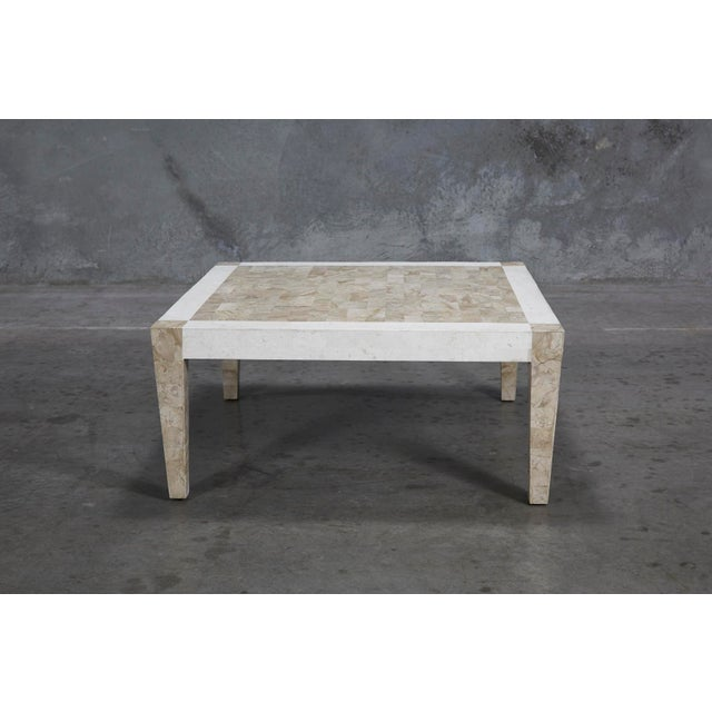 Simple and elegant modern form completely covered in tessellated stone over a fiberglass body. Legs and center of tabletop...