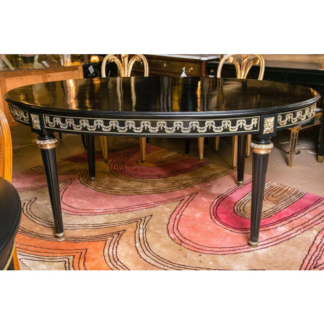 A French Louis XVI style gilt metal mounted mahogany ebonized dining table by Jansen. The table has an oval top that is...
