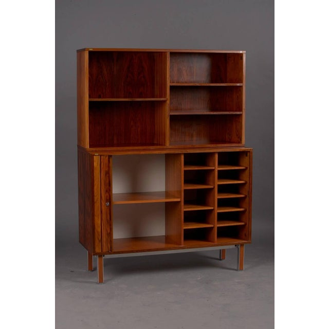 """Danish rosewood tambour door wall unit by Thorengaard. Measures: Base: 47.25"""" L x 17.75"""" W x 36.25"""" H; Bookcase: 47.25"""" L..."""