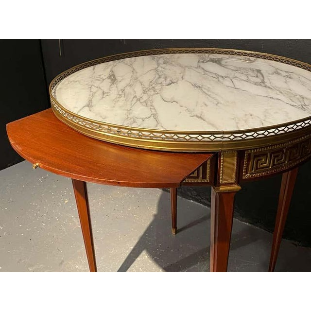 A pair of marble top Greek Key Bouillotte or end tables. Manner of Jansen in mahogany with double drawers and pull-out...