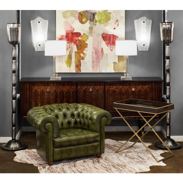 English vintage Chesterfield club chair with green, tufted leather upholstery, rolled arms, and wooden bun feet. So...