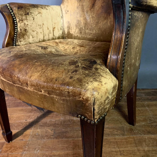 A diminutive English library armchair from the early 1900s - with darkening of original light-colored leather to a vintage...