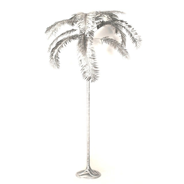 Pair of American aluminum palm trees with a spread of leaves emanating from a tiered shaft on a round molded base (signed...