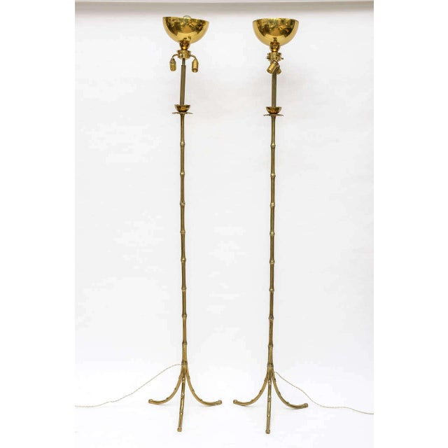 Rare pair of floor lamps. Faux bamboo legs rising up to a palm tree canopy just under the shade (not supplied). Double...