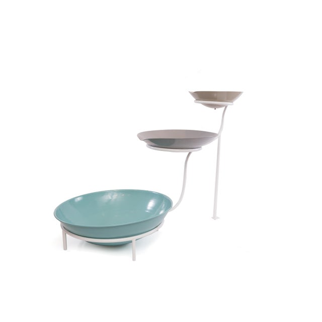 This whimsical fountain in powder-coated steel features three tiers, each with a pastel colored basin in graduated size.