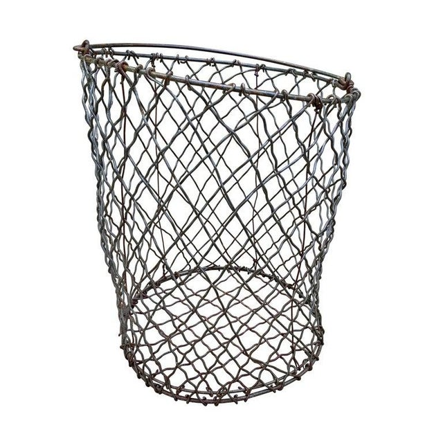 A wonderful vintage American industrial woven wire basket of round form with a handle, and groovy wonky form. Perfect for...