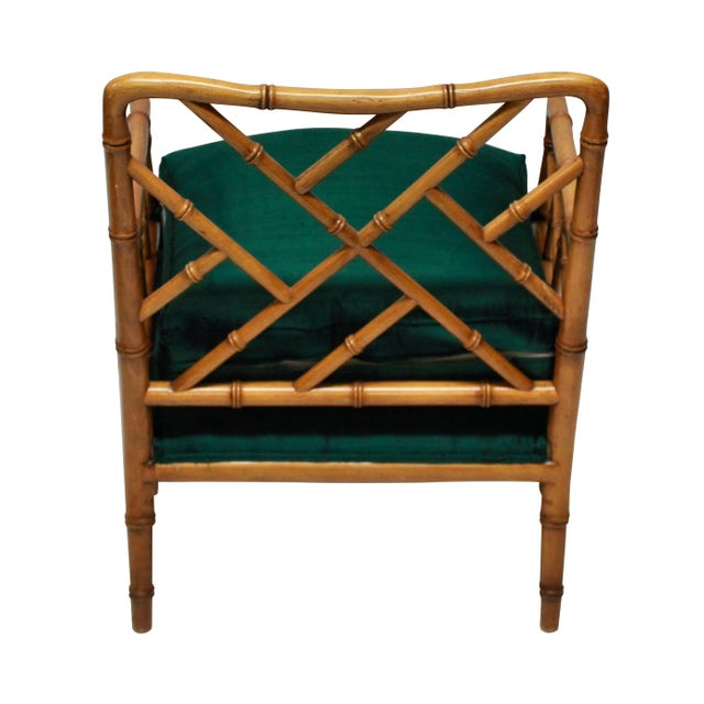 A pair of American faux bamboo cockpen deep armchairs, with newly upholstered emerald green silk seats.