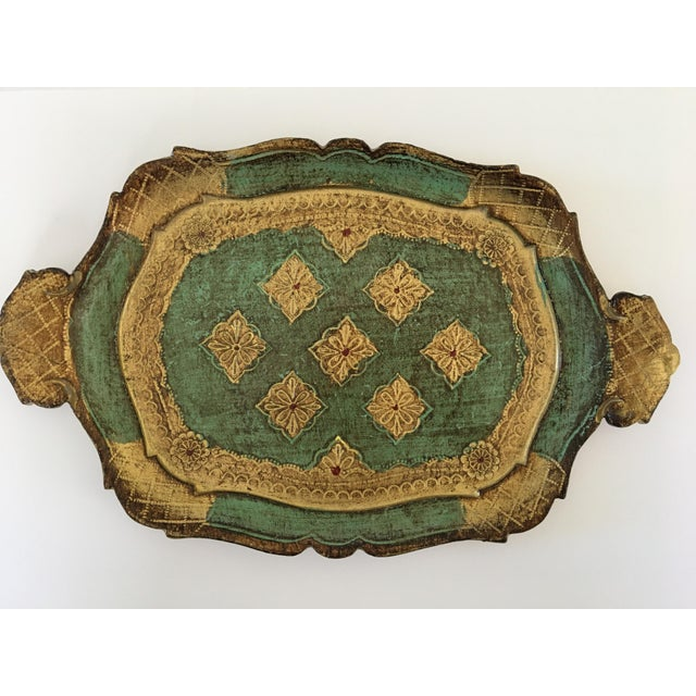 Offering a lovely, vintage, Florentine lacquer wooden gilt tray made in Italy. This handled tray has a makers mark and...
