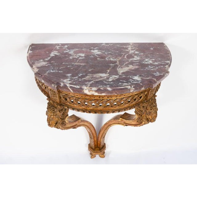 19th century French giltwood wall-mounted console with original marble. Very finely carved with ram's head motif.