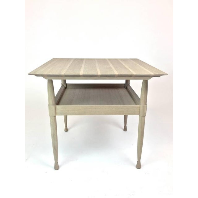 A silver grey finished mahogany side table with tray shelf. The top is striped in two tones of wood, and is supported on...