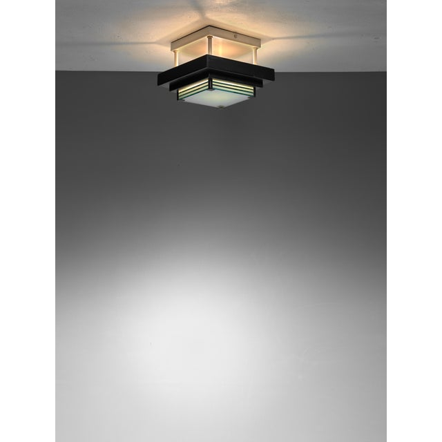 A French mid-century flush mount ceiling lamp. The lamp is made of a black and white metal frame, holding six blueish...