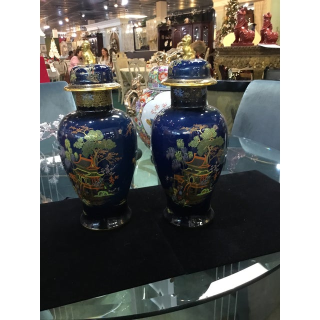 Very hard to find a pair of hand painted antique urns with lids and foo dog finials. These are English Carleton ware c...