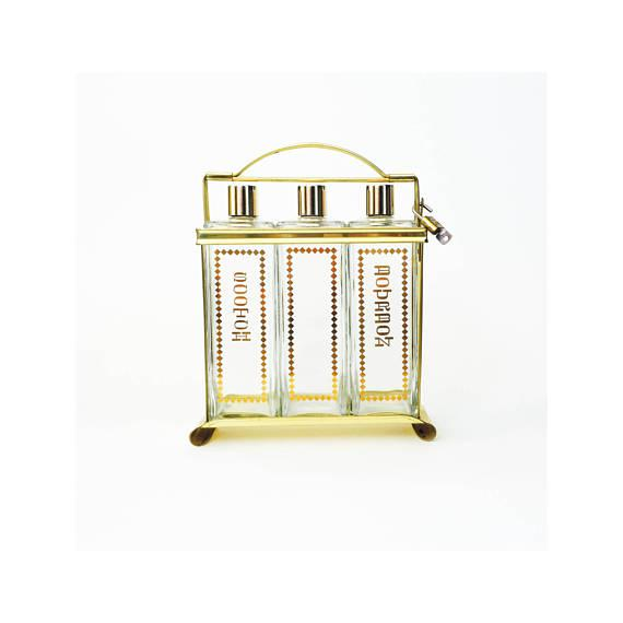 A mid century set of 3 glass decanters in a lockable brass caddy. Each of the rectangular decanters are made of thick...