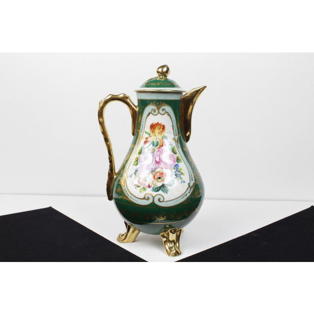 French hand-painted teapot with gold handle, feet and topper. Makers mark on the underneath of one foot and signed and...