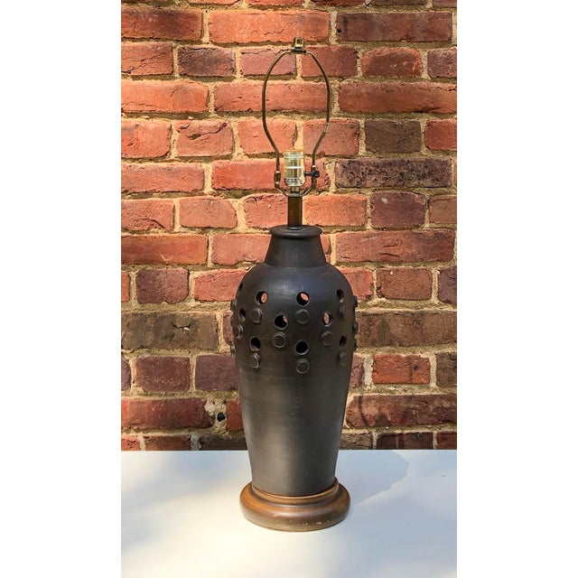 A rounded ginger jar shaped lamp with slate gray glaze with incised holes and raised divots on raised metal base. The Aldo...
